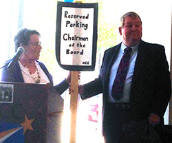 Carolyn Morton joking displays  reserved parking sign with NECC Chairman William J. Moynihan.