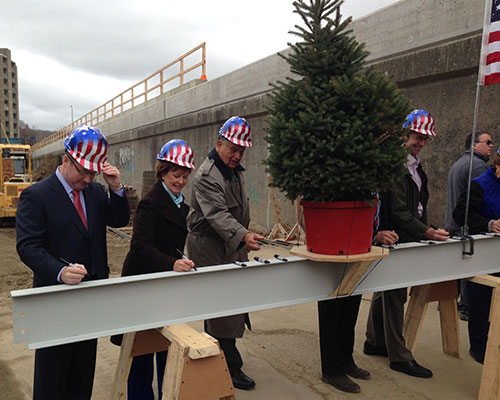 Officials add their signatures to the beam which will be moved to the top of the project.