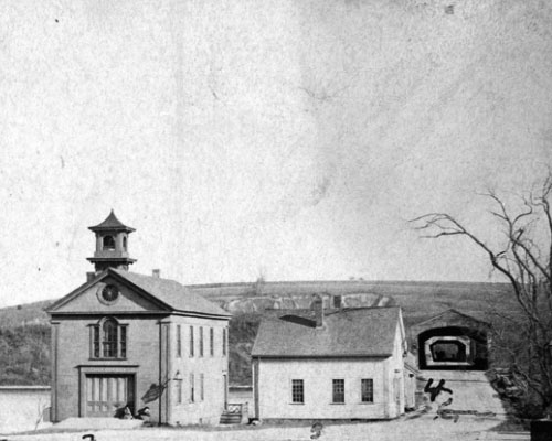 The Rocks Village Toll House in its original location (barely seen) at the entrance to the covered bridge. In the foreground are the Rocks Village Fire Station and a building described as a store or shop. (From the Collections of The Henry Ford.)