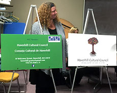 Artist Emily Boulger shows the new Haverhill Cultural Council logo in both English and Spanish. (WHAV News photograph.)