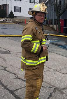Deputy Fire Chief Jeffrey Akstin surveys continuing hot spots. (WHAV News photograph.)