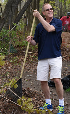 City Councilor Thomas J. Sullivan rakes leaves along the trail.