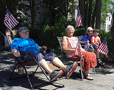 A group of Haverhill residents take in the procession along its route to Haverhill High School. From left are, Mark Courtney, Joann Ware, Barbara Courtney and seated in her lap, Johnny Portillo, Pheasant Lane. (Frank Komola photograph for WHAV News.)